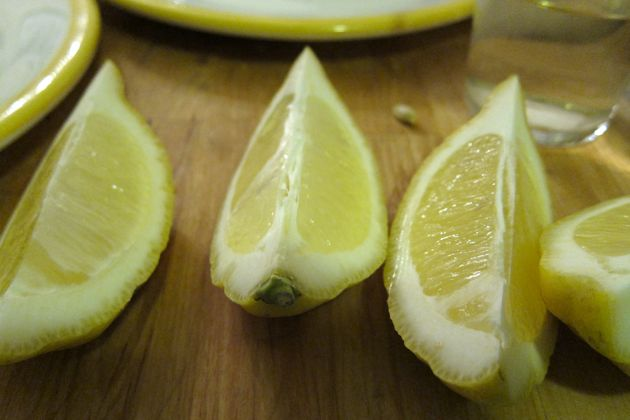 Lemon wedges sitting on a slab of wood with plates in the background.