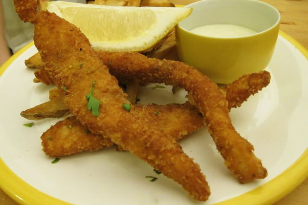 Fried salmon on a plate with a lemon wedge and a dish of dipping sauce served with french fries.