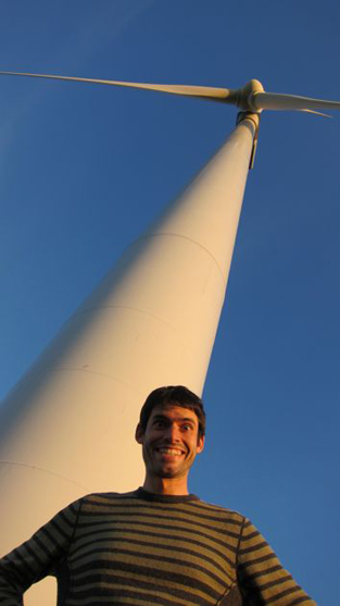 a man stands at the base of a windmill in Minnesota
