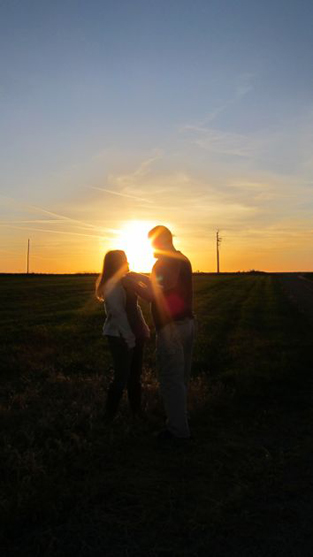 a couple at sunset on a windfarm