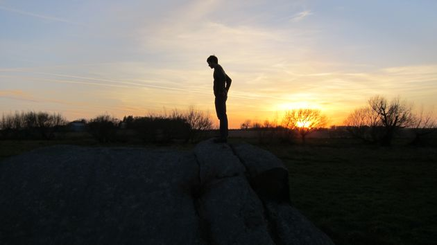 silhouetted man against the sunset on a glacier rock