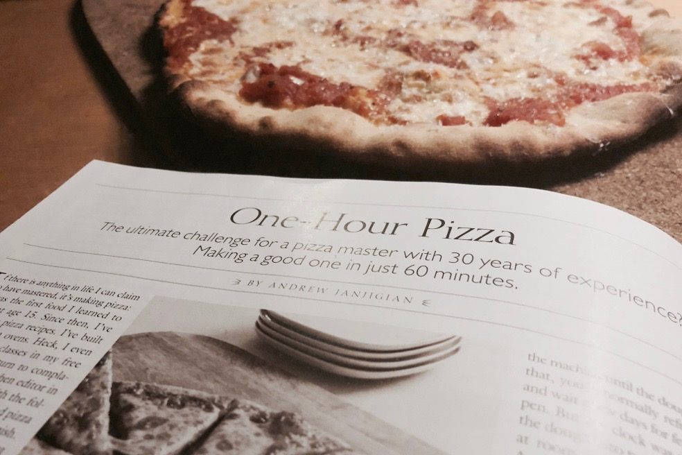 Cook's Illustrated magazine alongside a pizza made from the recipe shown