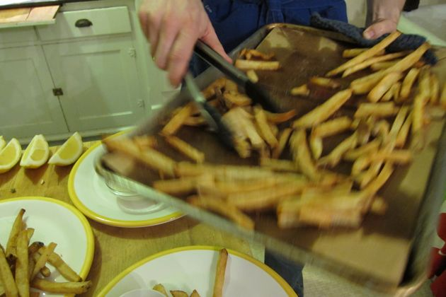 Tom adds fries to the plates for dinner from a jelly roll pan using tongs.