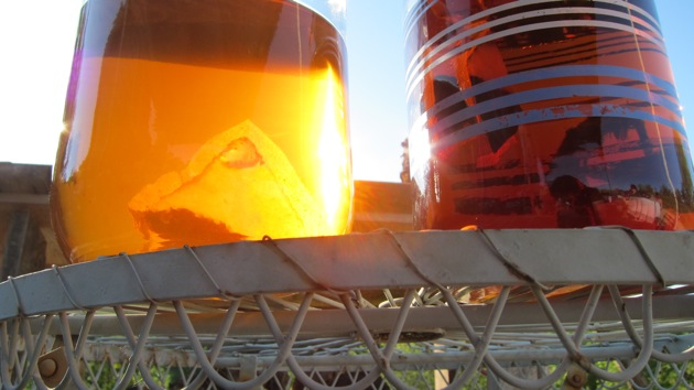 two jars of sun tea on a white metal cafe table in the sun light