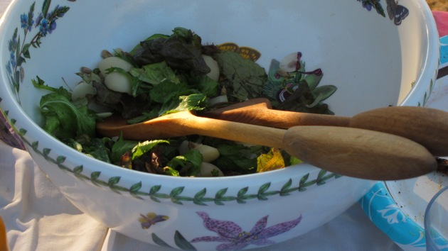 a potluck salad in a white bowl with wooden serving spoons