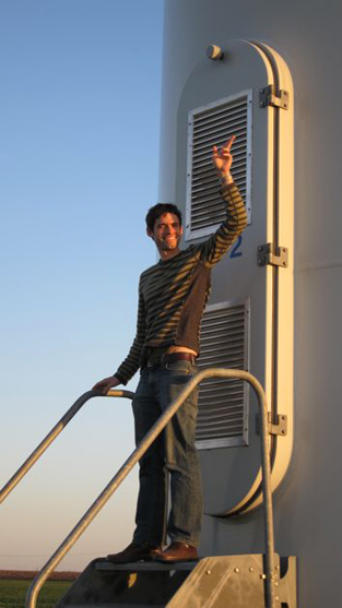 a man stands in front of a windmill's base and waves, as if he were the president getting out of Air Force One