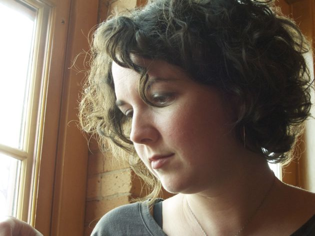 a portrait of a woman with curly hair near a window