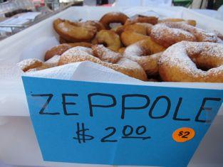 a box of Zeppole, $2.00 on a blue sign