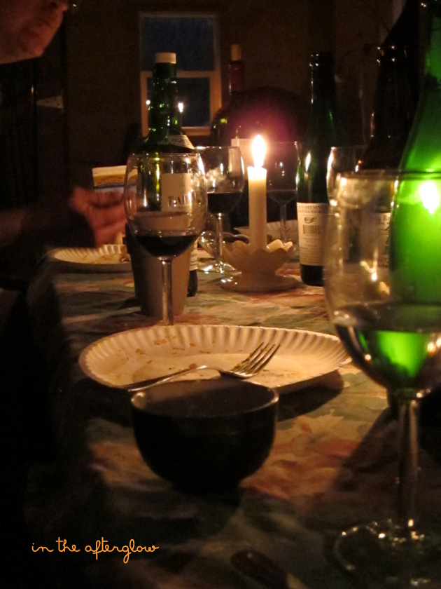 a candlelit tablescape after dinner with empty paper plates from dessert