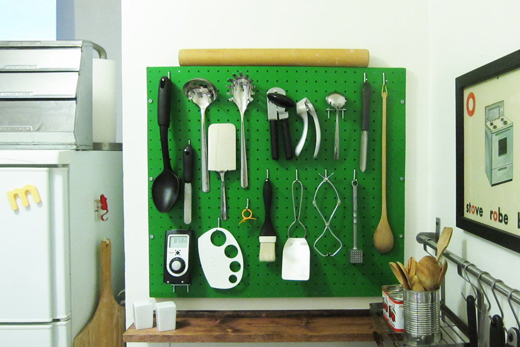 kitchen peg board painted bright green with utensils hanging