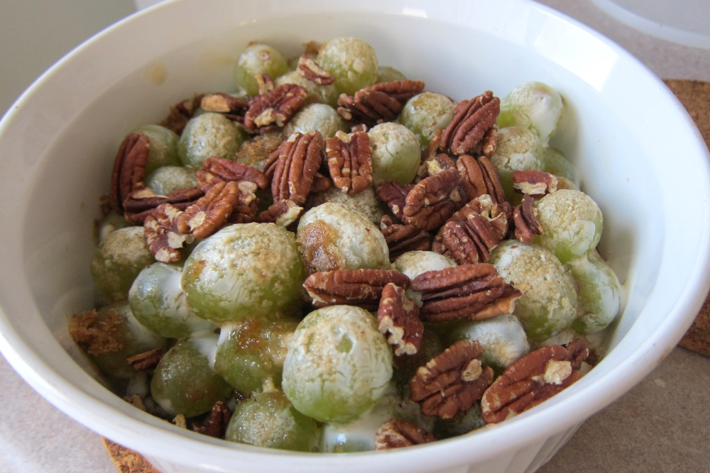 photo of bowl of green grapes covered in sour cream with caramelized brown sugar and pecans